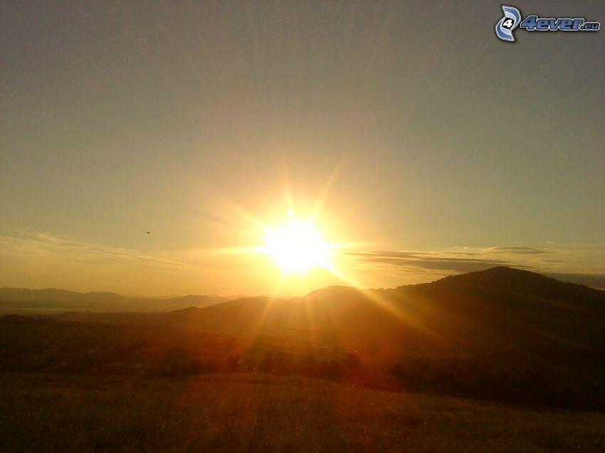 solnedgång bakom bergen, bergskedja, utsikt över landskap