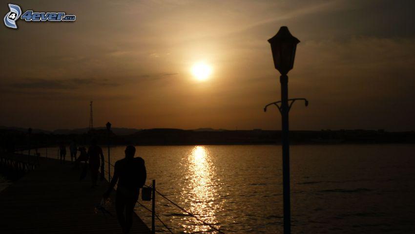 solnedgång över sjö, kust, lampa, silhuetter av människor