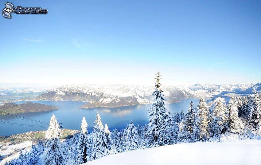 utsikt över landskap, sjö, snöig skog, kullar