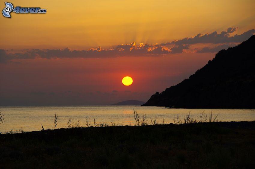 lugn sjö på kvällen, solnedgång bakom sjö