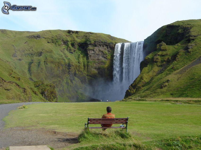 man på bänk, vattenfall, gräsmatta, kulle