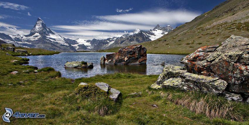 Matterhorn, tjärn, klippor, snöklädda berg, gräs