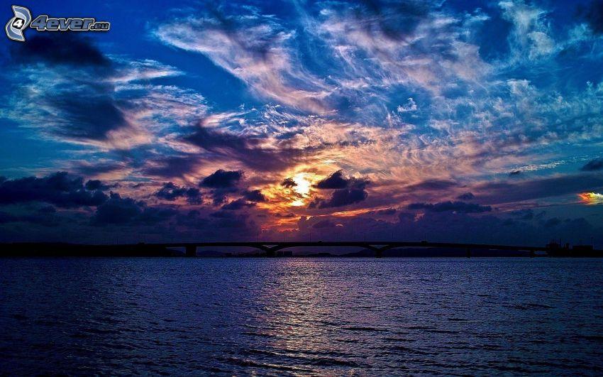 mörk solnedgång, solnedgång över flod, bro, silhuett, sol bakom molnen