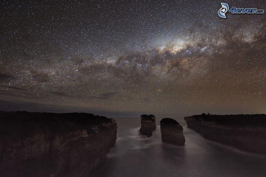 klippor vid kusten, hav, natthimmel, stjärnhimmel