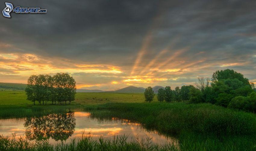 sjö, grönska, solnedgång bakom bergen, moln, solstrålar