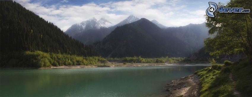 sjö, kullar, barrskog, snöklädda berg