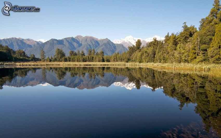 sjö i skogen, bergskedja, lugn vattenyta, spegling