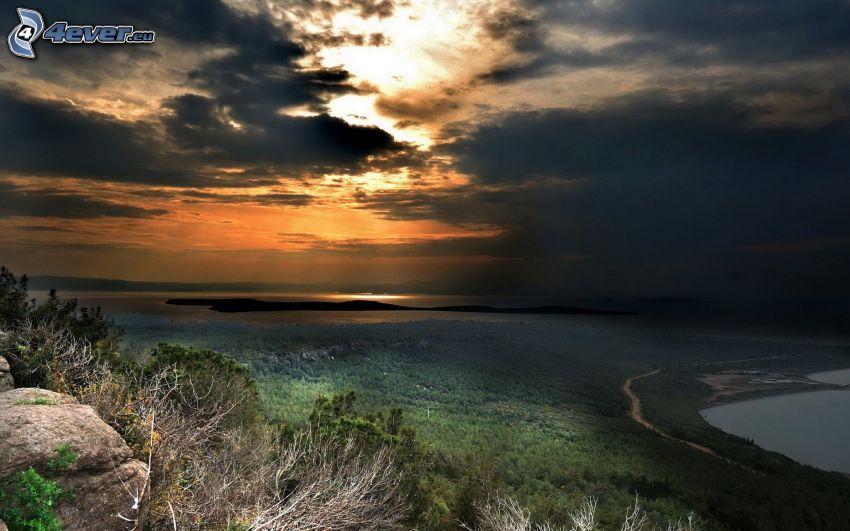 skog, mörk himmel, sol bakom molnen, sjö