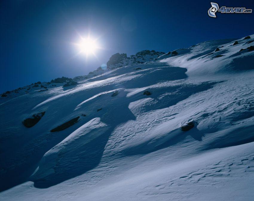 snöig backe, sol