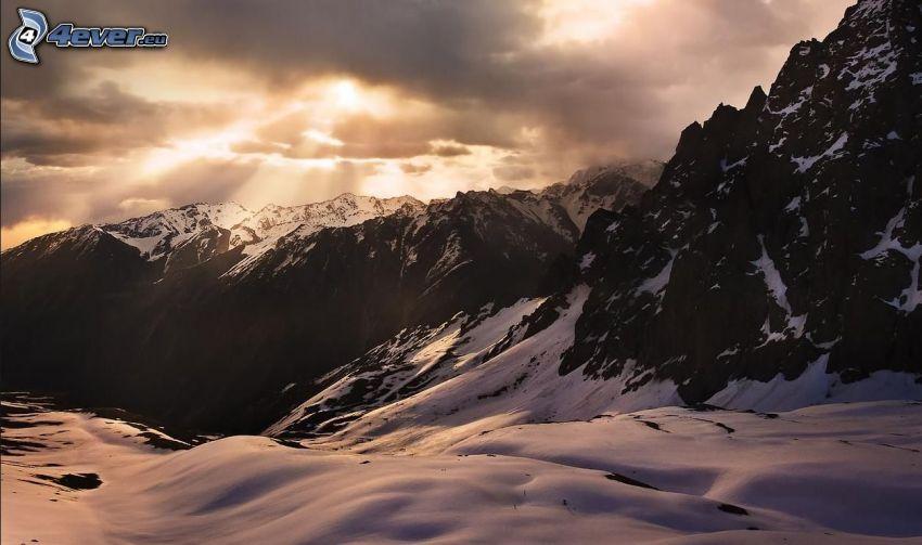 snöklädda berg, klippiga berg, höga berg, solstrålar bakom moln