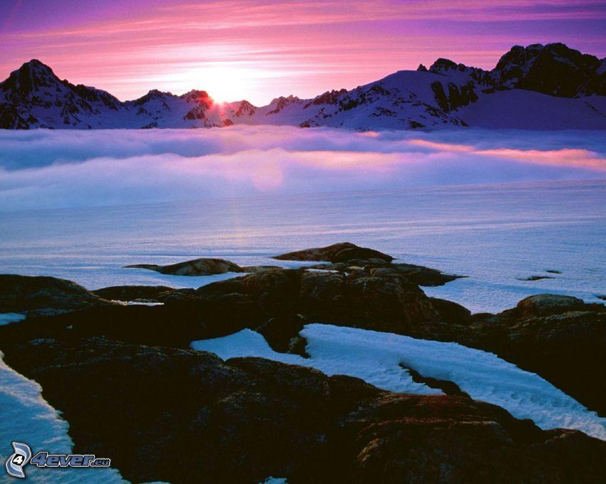 solnedgång bakom bergen, bergskedja, snö, klippor, lila himmel, inversion