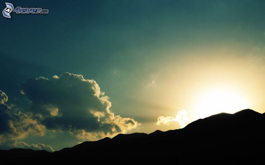 solnedgång bakom bergen, bergskedja
