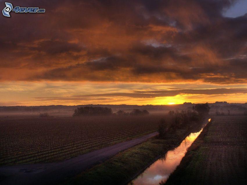 solnedgång bakom fält, bäck, väg