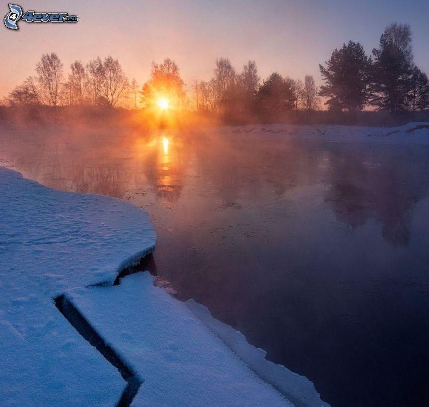 solnedgång bakom sjö, isflak