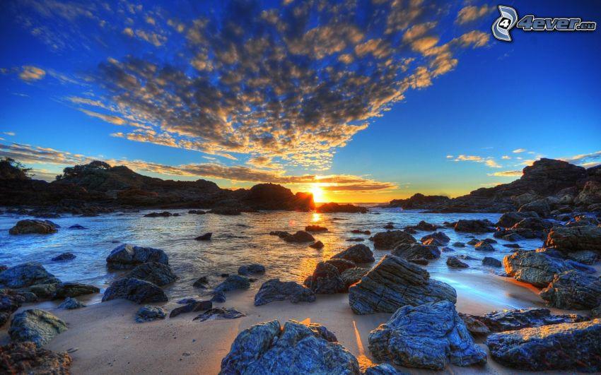 solnedgång bakom sjö, klippor, HDR