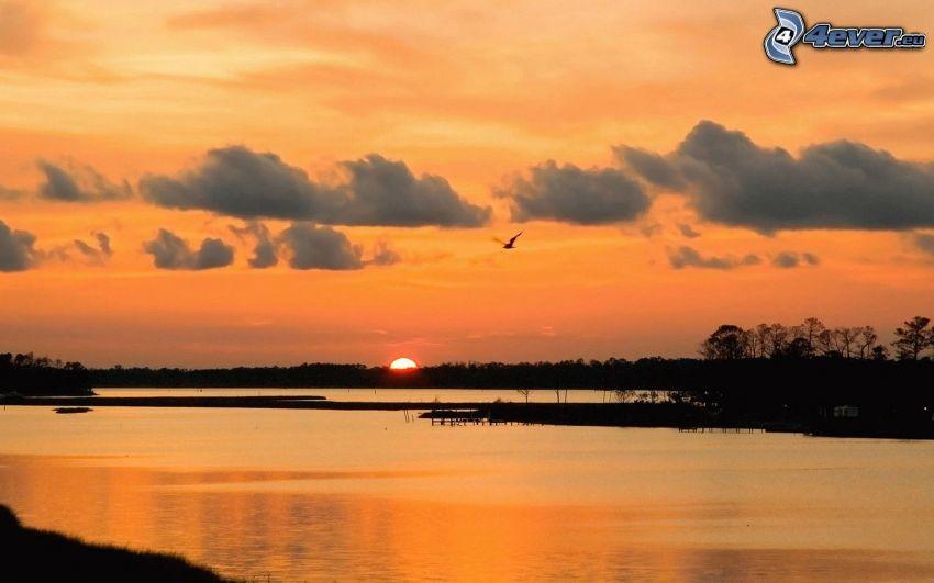 solnedgång bakom sjö, orange solnedgång, moln