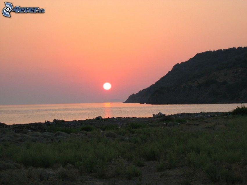 solnedgång bakom sjö