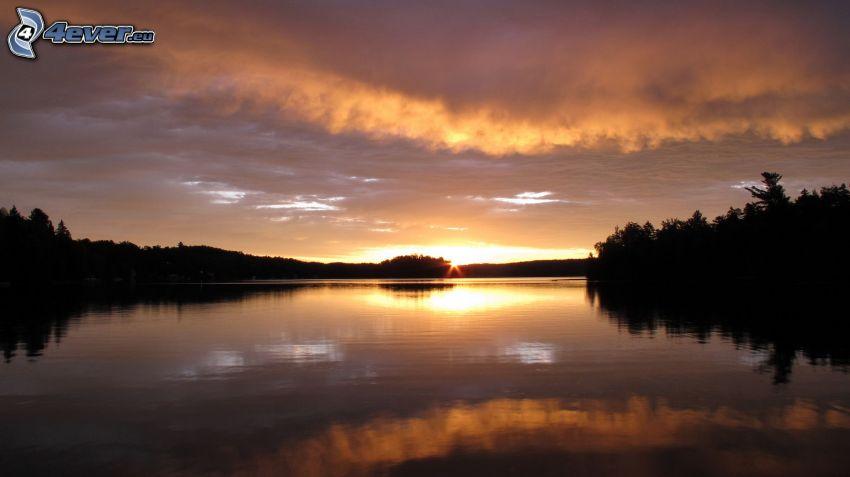 solnedgång över flod, kvällshimmel, siluetter av träd