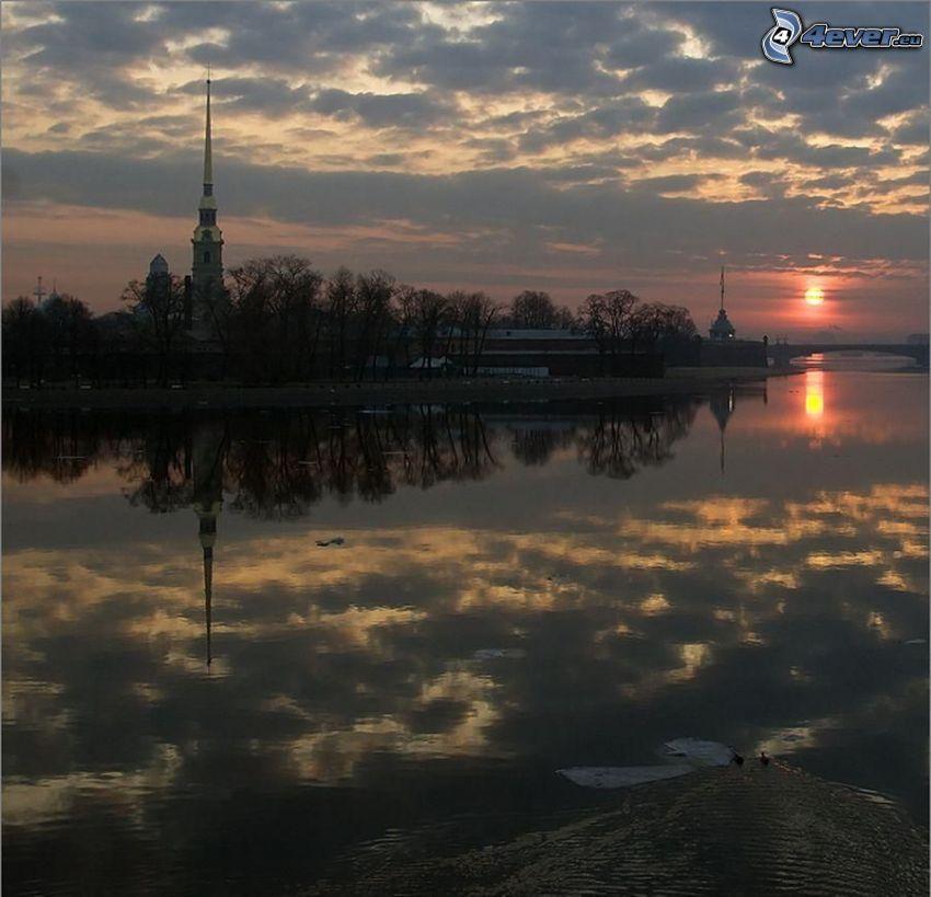 solnedgång över flod, kyrka, moln