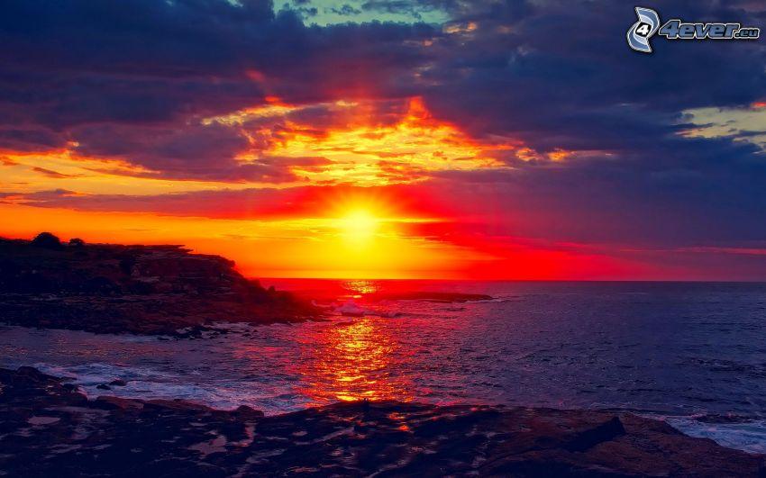 solnedgång över hav, öppet hav, stenig kust, moln