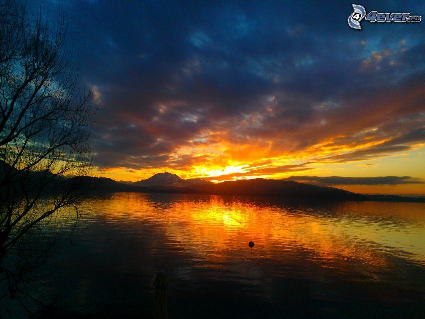 solnedgång över kulle, sjö