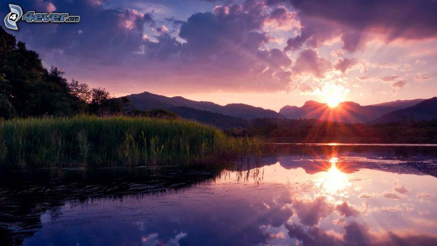 solnedgång över sjö, bergskedja