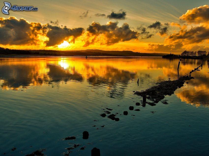 solnedgång över sjö, moln