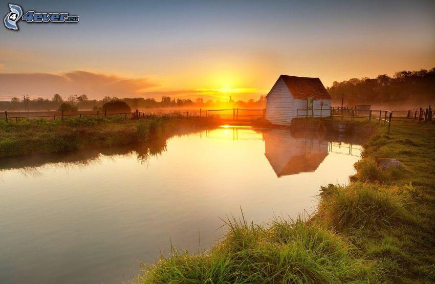solnedgång över sjö, stuga