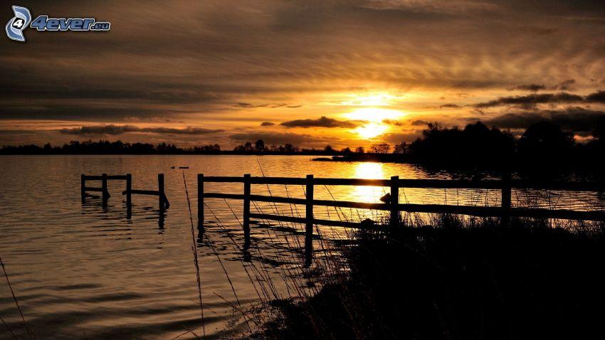 solnedgång över sjö, trästaket