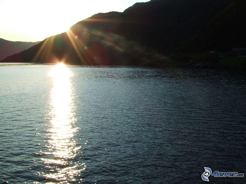 solnedgången över sjö, berg, reflektion av solen
