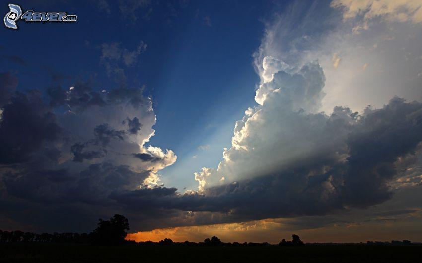 solstrålar bakom moln, solnedgång
