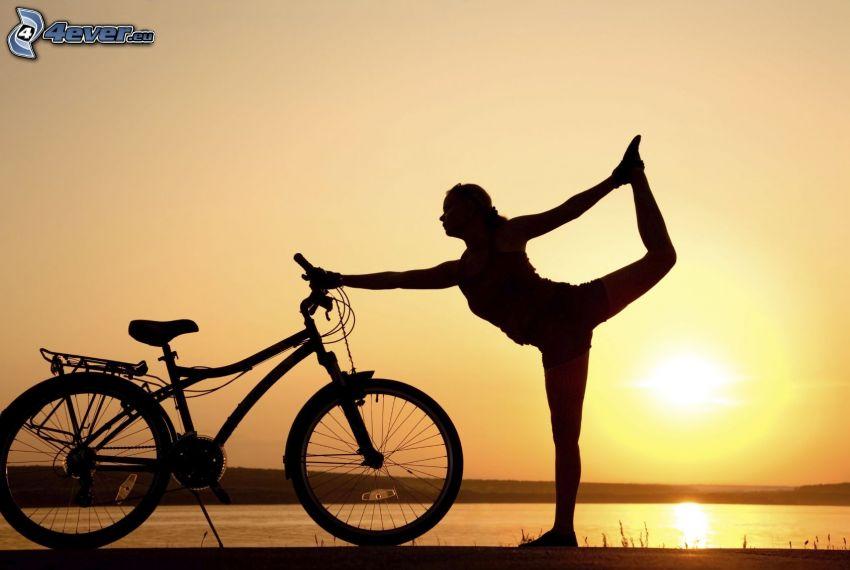 silhuett av kvinna, yoga, cykel, solnedgång, gul himmel