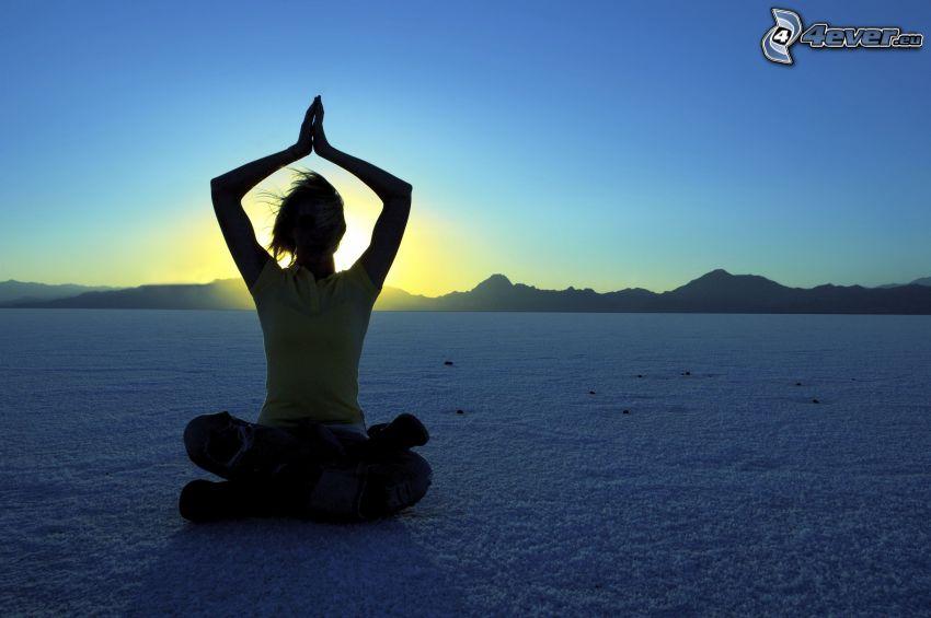 yoga, benen i kors, solnedgång över kulle
