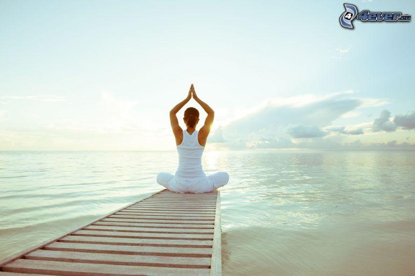 yoga, meditation, benen i kors, öppet hav, träbrygga
