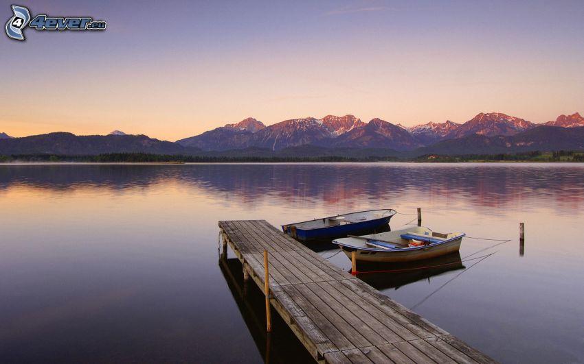träbrygga, båtar vid strand, bergskedja