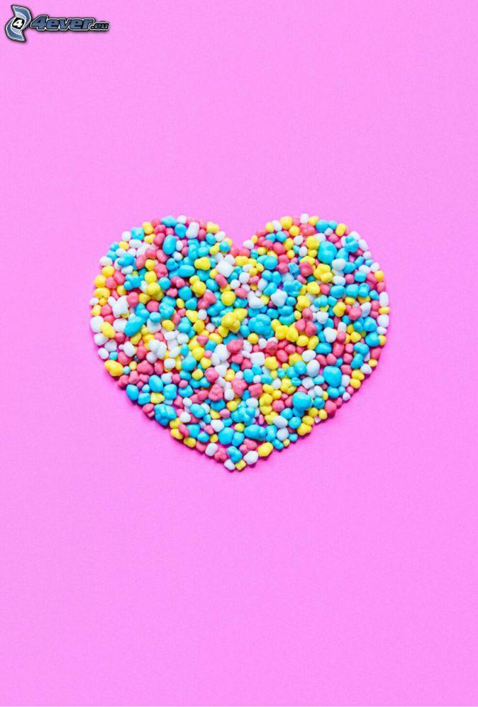caramelos, corazón, fondo de color rosa