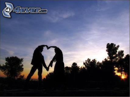corazón de las manos, silueta de una pareja, bosque después de la puesta del sol