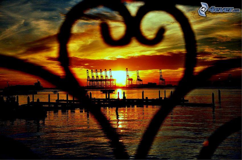 puesta de sol en el puerto, valla, corazón