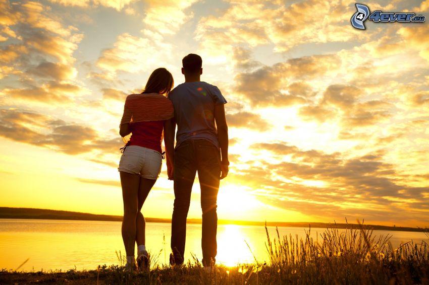 pareja, puesta de sol sobre un lago