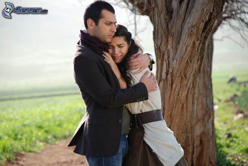 pareja al lado de un árbol, abrazar, tristeza
