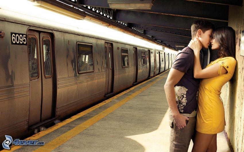 pareja en abrazo, beso suave, metro