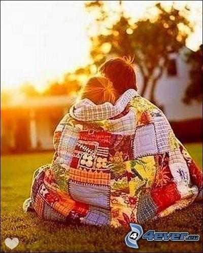 pareja en abrazo, manta, parque al atardecer