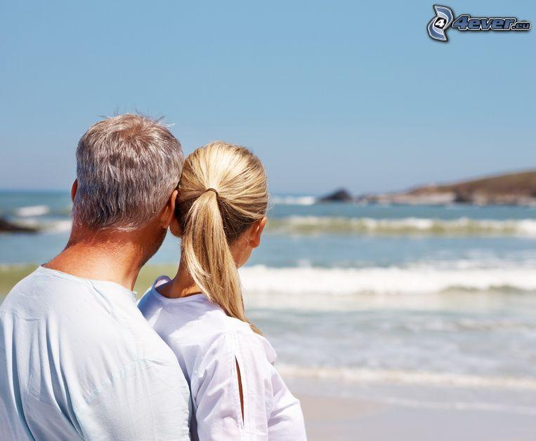 pareja en abrazo, mar, olas en la costa