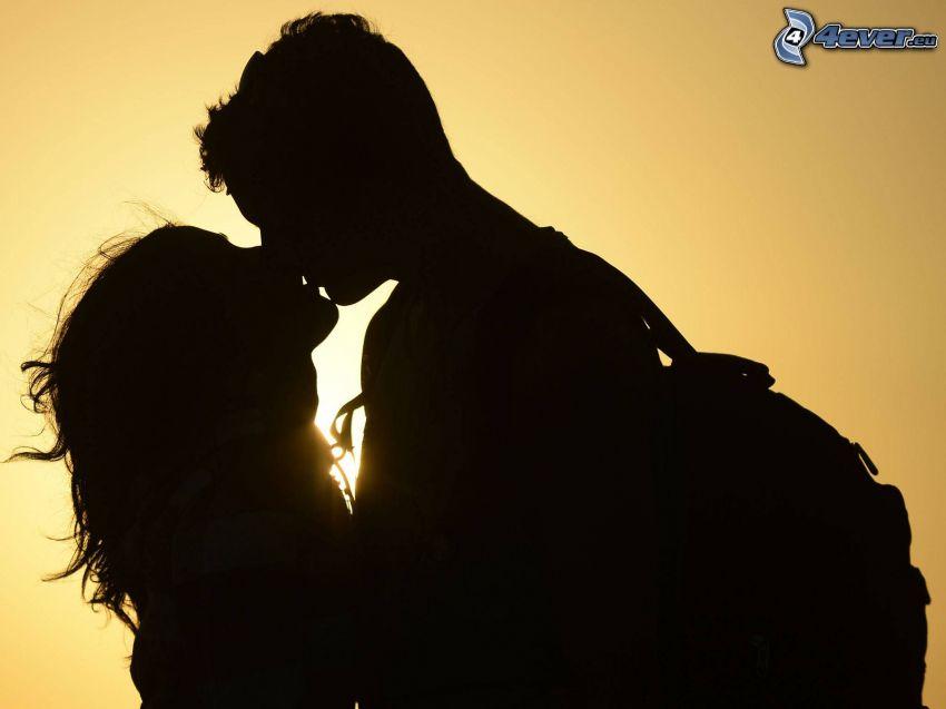 silueta de una pareja, beso, sol