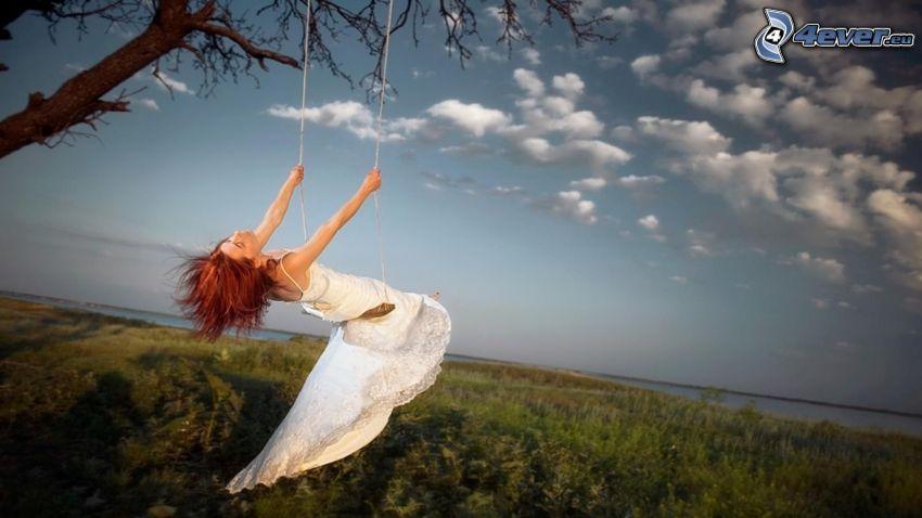 mujer en un columpio, nubes, prado