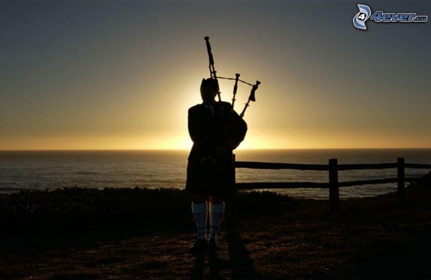tocando la gaita, puesta de sol en el mar