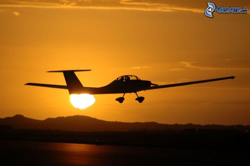 VGS Cadet, pequeño avión deportivo, despegue al atardecer, cielo anaranjado