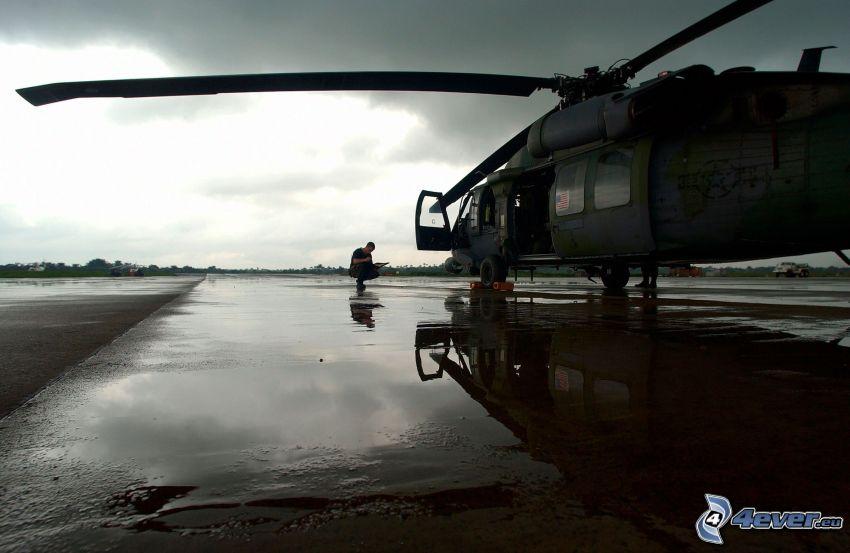helicóptero militar, hombre, charco