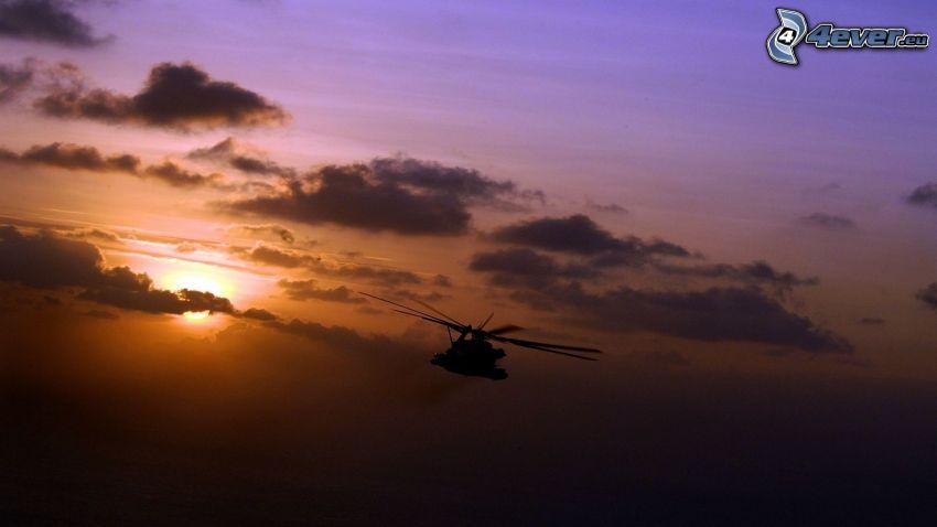 silueta del helicóptero, puesta de sol en las nubes