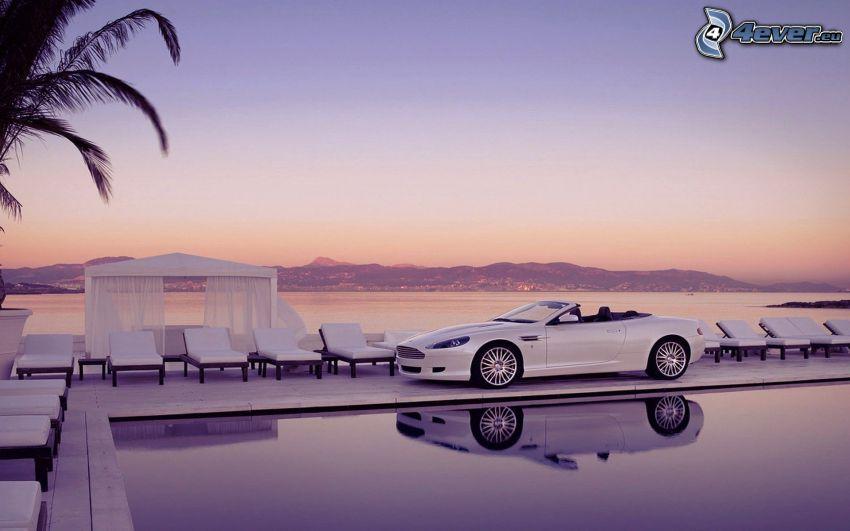 Aston Martin DB9, descapotable, piscina, sillas, mar, después de la puesta del sol, cielo púrpura